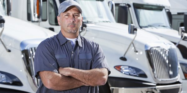 Truck driver (30s) standing in front of row of semi-trucks.